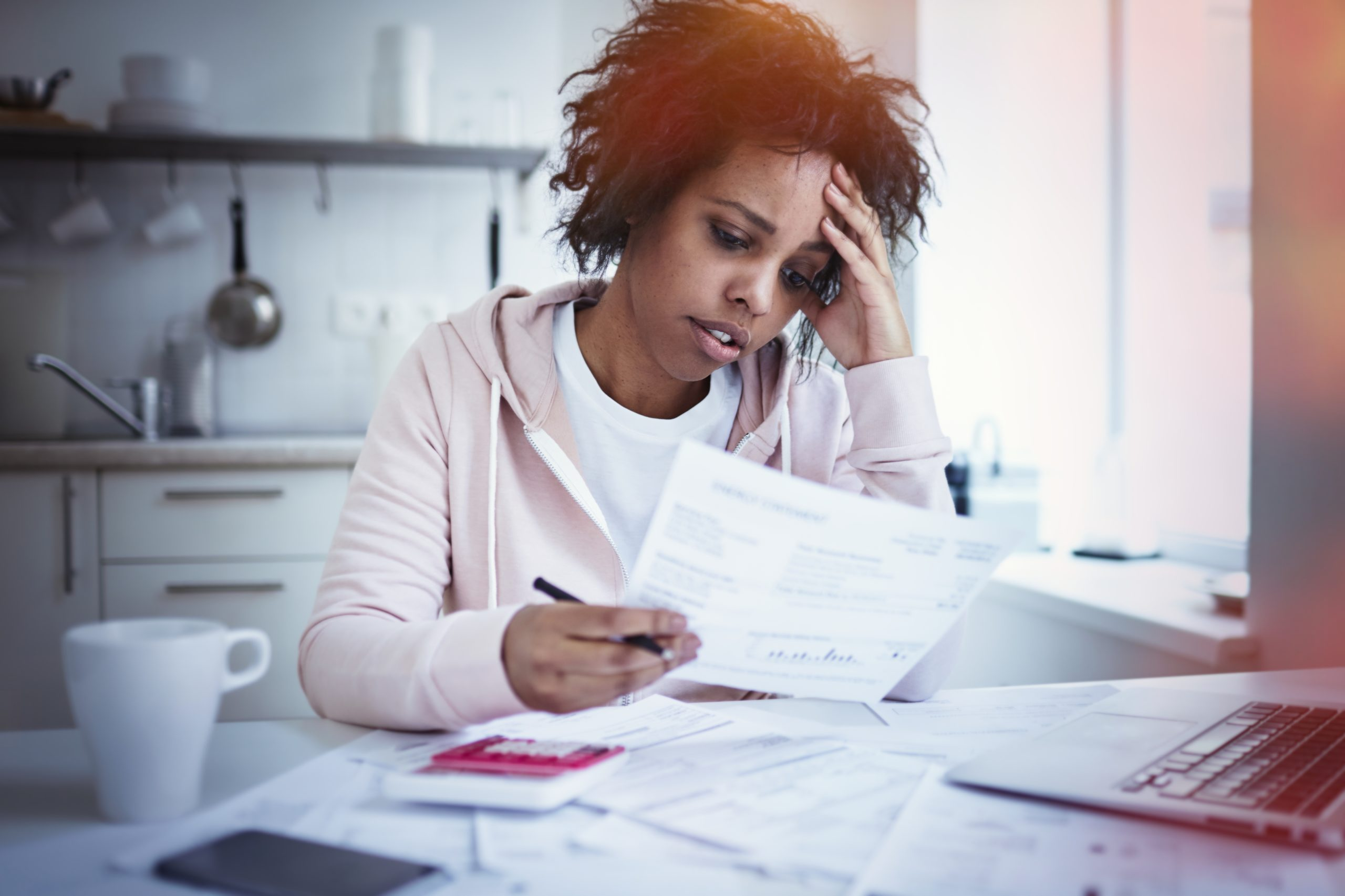 Young upset african american female sitting at kitchen table with laptop dealing with financial stress feeling pressure because of mortgage debt worrying a lot or feeling anxious over money